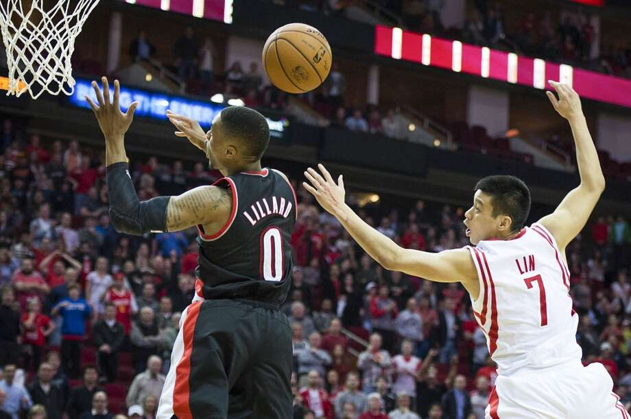 Rockets point guard Jeremy Lin picks up a steal as he knocks the ball away from Trail Blazers point guard Damian Lillard with 7.9 seconds left to play for a turnover that sent the game into overtime. Photo: Smiley N. Pool, Houston Chronicle