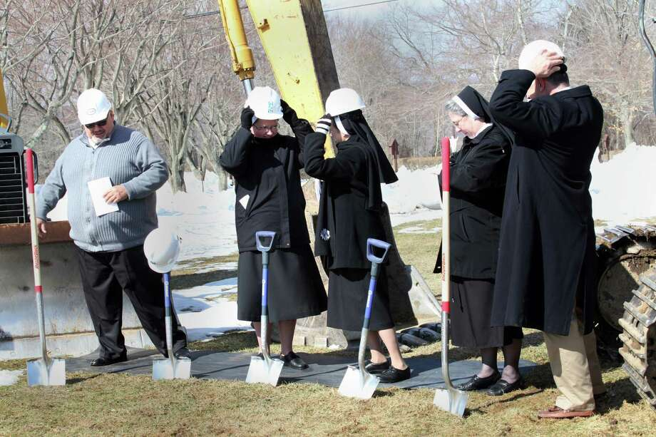 Putting on their hard hats , from left, Tom Augustino, Mother Jana Zawieja, Sister Barbara Jean Wojnicki, Sister Teresa Mika, and John Kimball, dig in for the groundbreaking of the new convent in Monroe, Conn. on Sunday March 9, 2014. Photo: BK Angeletti, B.K. Angeletti / Connecticut Post