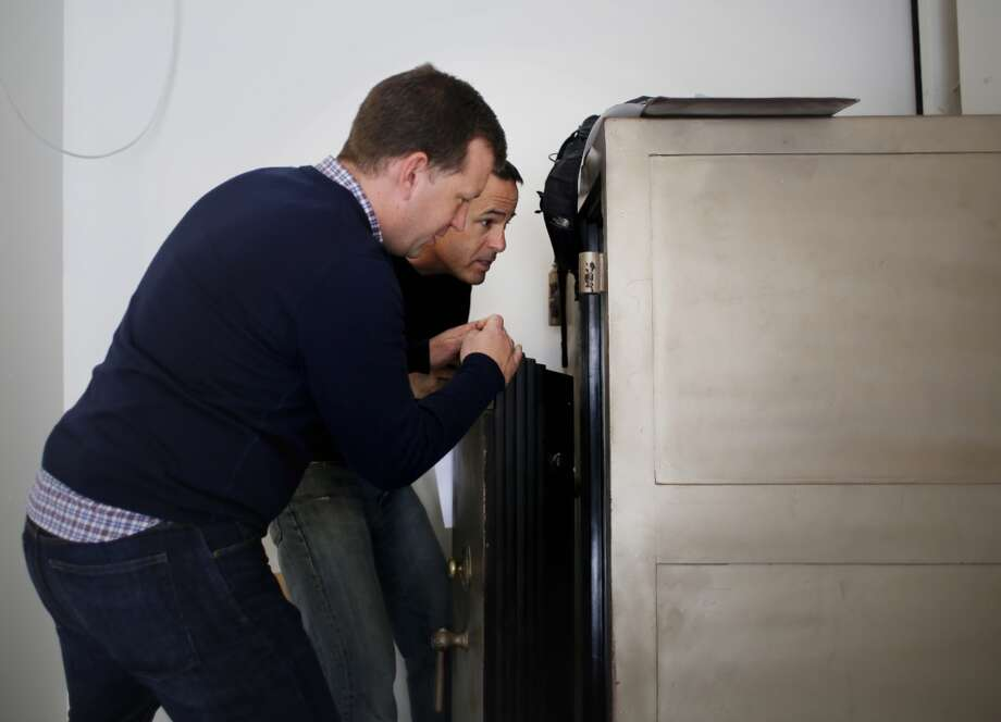 Homeowner Christian Rodgers and hobbyist safecracker Mike Wyatt investigate the inside of the newly opened antique safe in the Upper Castro neighborhood of San Francisco. Photo: The Chronicle