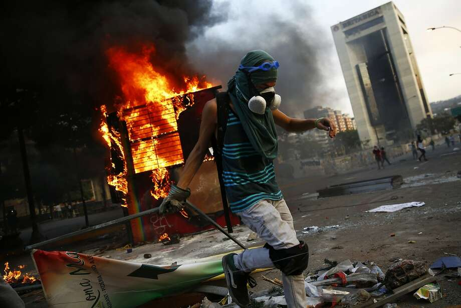 An anti-government protester sets up a barricade next to a burning kiosk during a protest at Altamira square in Caracas March 9, 2014. Latin American foreign ministers will meet next week to discuss the unrest in Venezuela that has left at least 20 dead and convulsed the South American OPEC nation, diplomatic sources said on Friday. REUTERS/Jorge Silva (VENEZUELA - Tags: CIVIL UNREST POLITICS TPX IMAGES OF THE DAY) Photo: Jorge Silva, Reuters