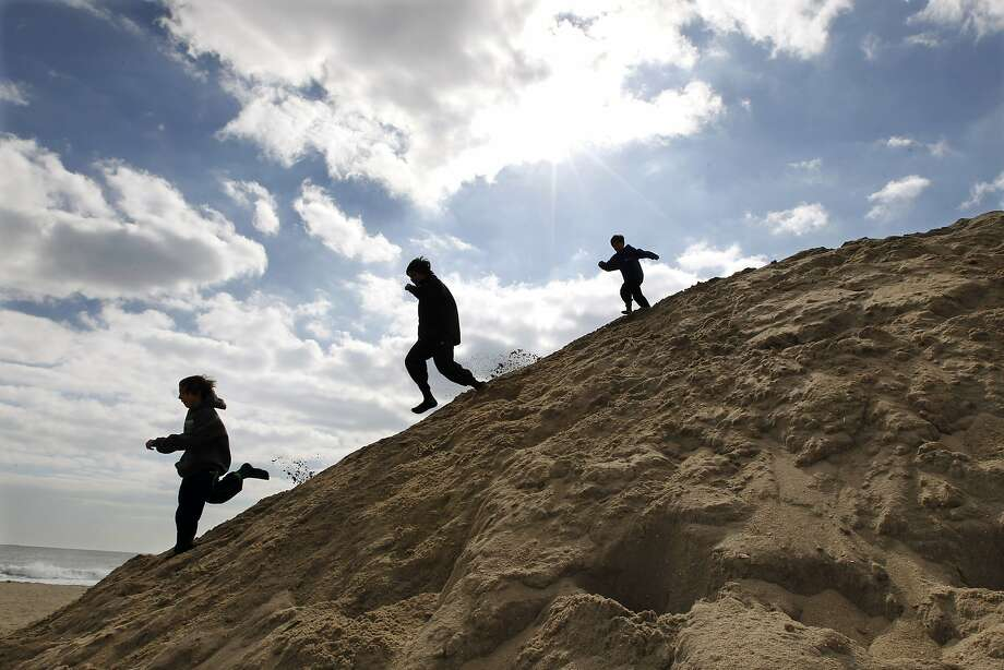 Children play on a large mound of sand on the beach early, Sunday, March 9, 2014, in Asbury Park, N.J. (AP Photo/Mel Evans) Photo: Mel Evans, Associated Press