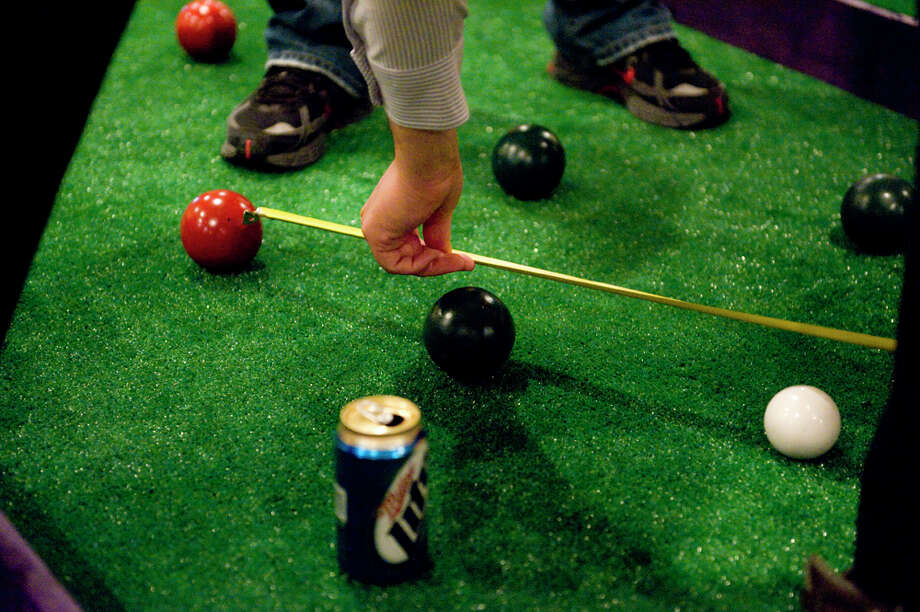 Speaking of bars, your neighborhood has gentrified if there is a popular bar with people playing Bocce ball (or cornhole, which a bean bag toss), instead of pool. Photo: Tom Williams, Roll Call Photos / Roll Call Photos