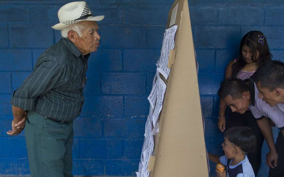 Voters search a list for the location of their respective polling tables during the presidential runoff election in Panchimalco, on the outskirts of San Salvador, El Salvador, Sunday, March 9, 2014. Salvadorans headed to the polls Sunday to elect their next president in a runoff between former Marxist guerrilla Salvador Sanchez Ceren from the ruling Farabundo Marti National Liberation Front (FMLN), and former San Salvador Mayor Norman Quijano from the Nationalist Republican Alliance (ARENA). (AP Photo/Esteban Felix) Photo: Esteban Felix, Associated Press