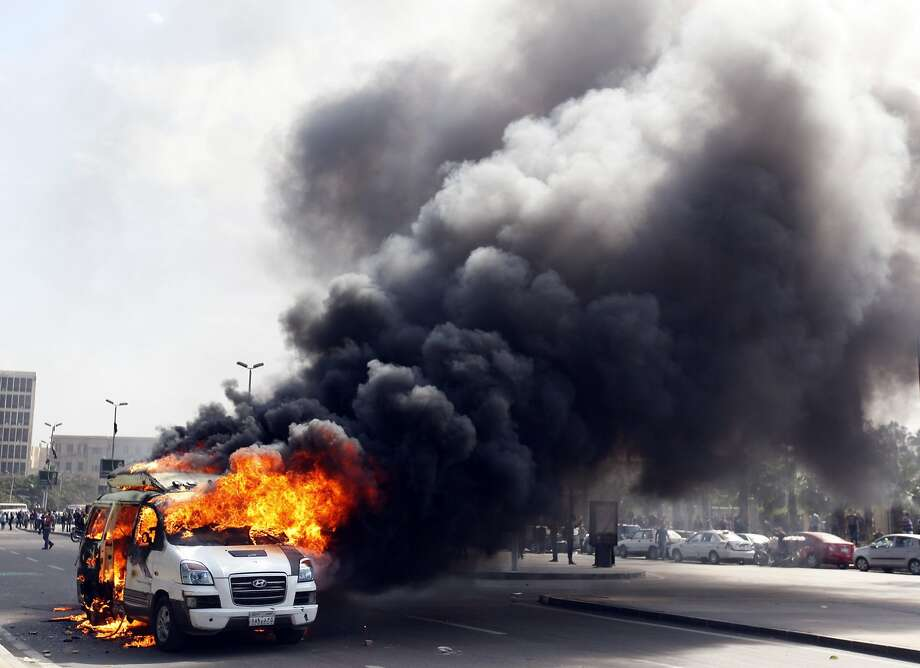 A car belonging to the media burns during a protest by supporters of the Muslim Brotherhood and ousted Egyptian President Mohamed Mursi inside Cairo University, in Cairo, March 9, 2014.  REUTERS/Mohamed Abd El Ghany (EGYPT - Tags: POLITICS CIVIL UNREST MEDIA TPX IMAGES OF THE DAY) Photo: Mohamed Abd El Ghany, Reuters