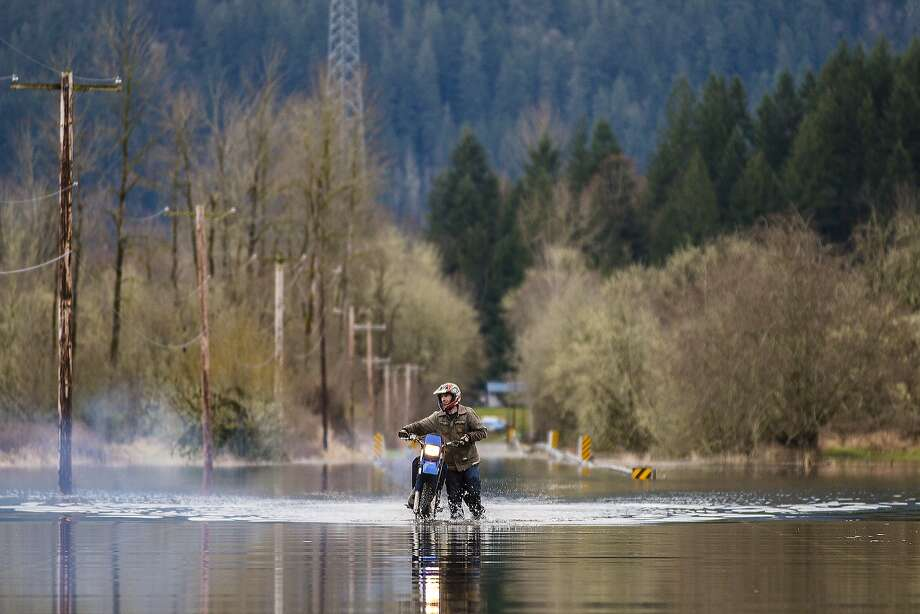 An unidentified man wades through flood water from the Cowlitz River with his motorcycle across a stretch of Peters Road in Randle, Wash., on Sunday, March 9, 2014. Heavy rain and warm temperatures in the Cascade Mountains over the past week has caused minor flooding along the Cowlitz River and its tributaries. The National Weather Service has projected the Cowlitz River to crest at 18.72 feet on Monday afternoon. That level is projected to cause minor flooding in the area. (AP Photo/The Chronicle, Pete Caster) Photo: Pete Caster, Associated Press