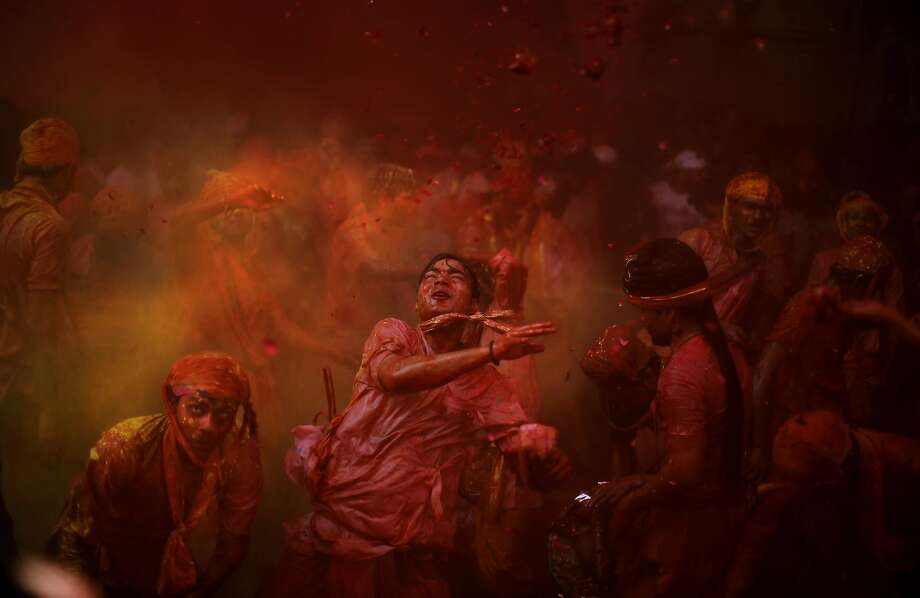 Hindu men from the village of Nangaon throw colored powder at each other as they play holi at the Ladali or Radha temple before the procession for the Lathmar Holi festival, the legendary hometown of Radha, consort of Hindu God Krishna, in Barsana 115 kilometers ( 71 miles) from New Delhi, India , in New Delhi, India, Sunday, March 9, 2014. During Lathmar Holi the women of Barsana beat the men from Nandgaon, the hometown of Krishna, with wooden sticks in response to their teasing as they depart the town. (AP Photo/Altaf Qadri) Photo: Altaf Qadri, Associated Press