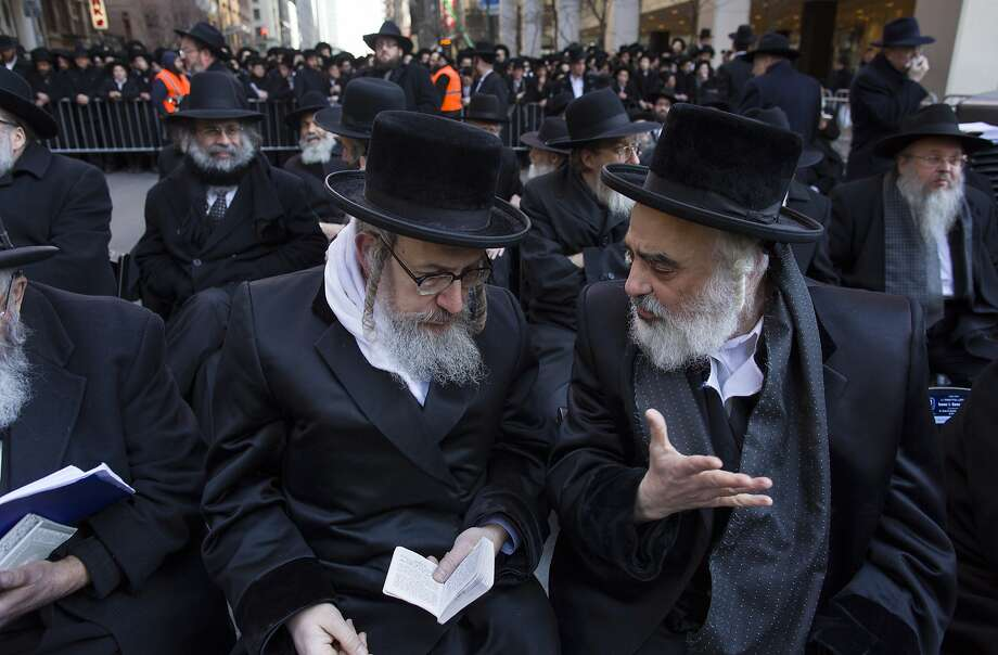 Rabbis speaks to one another as they joined other Orthodox Jews  in New York, Sunday, March 9, 2014, on Water Street in lower Manhattan, to pray and protest against the Israeli government's proposal to pass a law that would draft strictly religious citizens into its army. (AP Photo/Craig Ruttle) Photo: Craig Ruttle, Associated Press