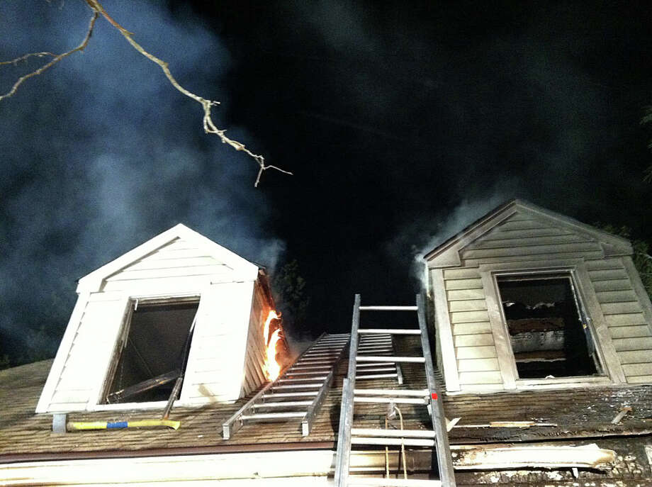 Fire caused heavy to damage to a Crane Street house early Monday, and two people were rescued from a second-floor bedroom. Photo: Fairfield Fire Department / Fairfield Citizen