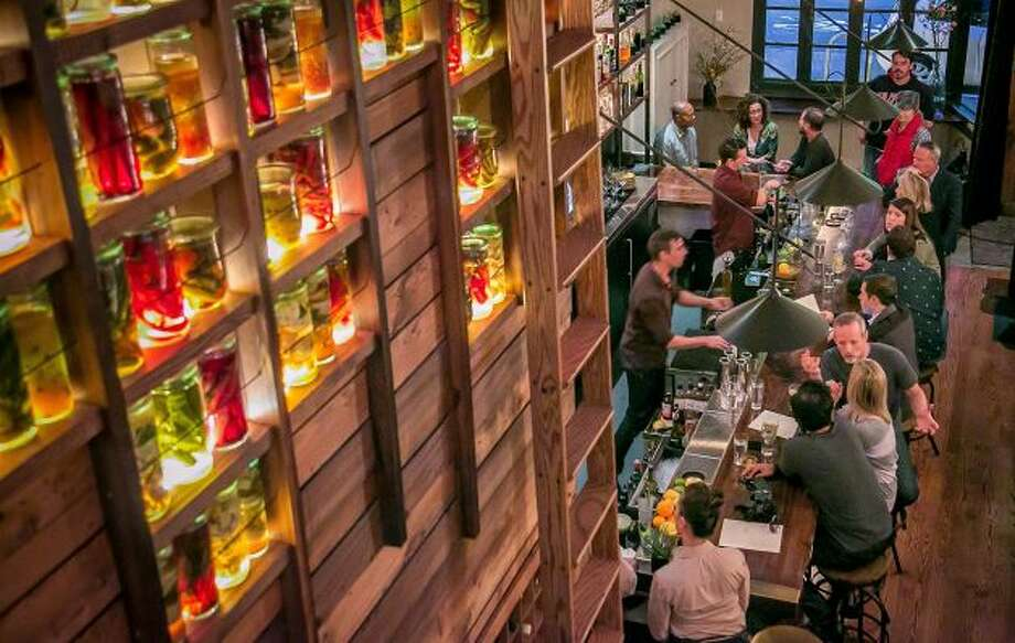 A room with lighted indentations filled with jars of house-preserved produce acts as a divider between the bar and dining room. Photo: John Storey, Special To The Chronicle