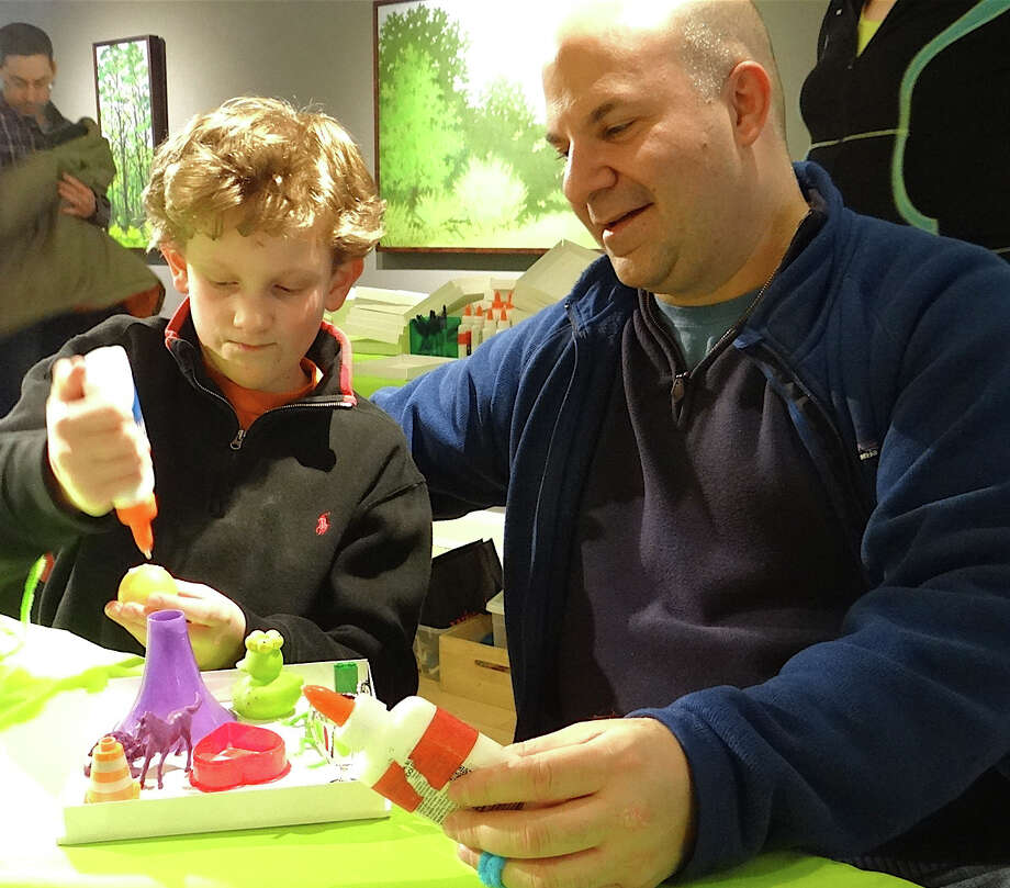 Marshall Kiev of Westport and son, Eddie, 11, collaborate on a box-top collage at the Westport Arts Center's Family Art Day on Sunday. Photo: Mike Lauterborn / Westport News