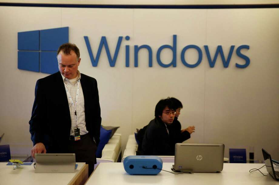 An employee inspects Windows powered mobile devices on display at a Microsoft Corp. news conference ahead of the Mobile World Congress in Barcelona, Spain, on Sunday, Feb. 23, 2014. (Simon Dawson/Bloomberg) Photo: Simon Dawson / © 2014 Bloomberg Finance LP
