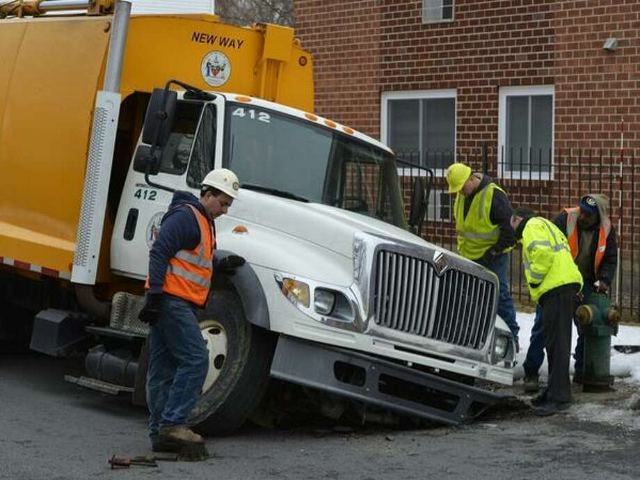 An Albany garbage truck  partially sank into  apparent sink hole on First Street on Monday. (Skip Dickstein / Times Union)