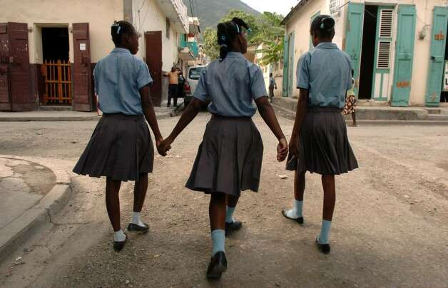 Uniformed school girls walk along a Cap-Haitien street in December 2009. Photo: Christian Abraham / Connecticut Post