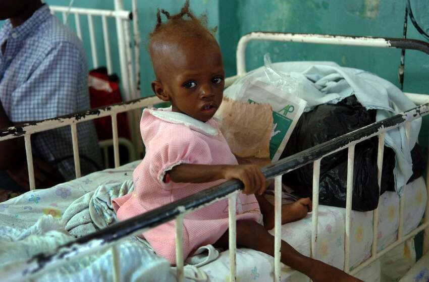 A young child sits in her crib at Justinien Hospital's pediatric ward, in downtown Cap-Haitien on Wednesday Dec. 16, 2009.