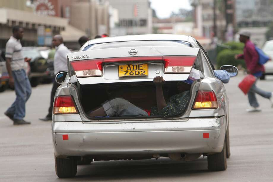 Zimbabwe's version of Uber:A private car operates as a cheap but illegal taxi in   Harare, with the fare riding in the trunk. Photo: Tsvangirayi Mukwazhi, Associated Press