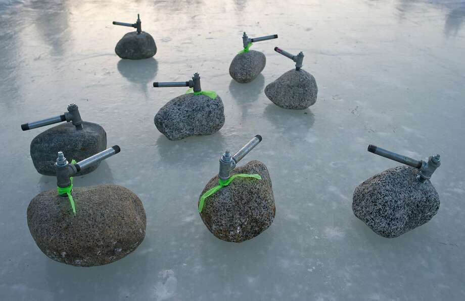 Old-school curling: You won't find any of those fancy polished Sochi curling stones on Alaska's Auke Lake, near in Juneau. Curlers here slide chunks of granite impaled with ice hammers. Photo: Michael Penn, Associated Press