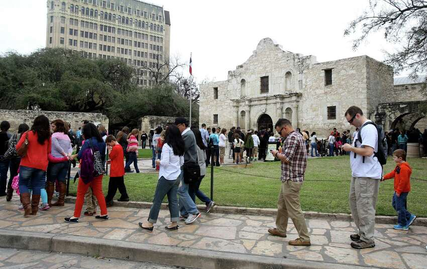 Visitors line the walkways at the Alamo on Monday March 10, 2014 to get a peek into the historic shrine on the first day of Spring Break.