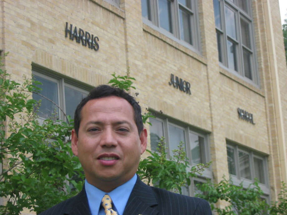 Former Harris Middle School Principal Moises Ortiz stands in front of the school in 2006. Photo: AMANDA REIMHERR, San Antonio Express-News / SAN ANTONIO EXPRESS-NEWS