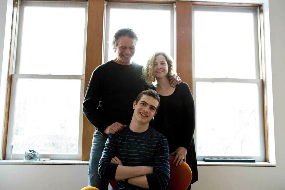 Louis Harboe, center, who got his first freelance tech job at age 12, with his parents, Frederik Harboe and Catherine Becker at their home in Chicago, March 3, 2014. For teenage designers of apps and games, there is much incentive, financial and otherwise, to skip the schoolwork and accelerate their transition into the business world. (Nathan Weber/The New York Times) ORG XMIT: MER2014030715482125