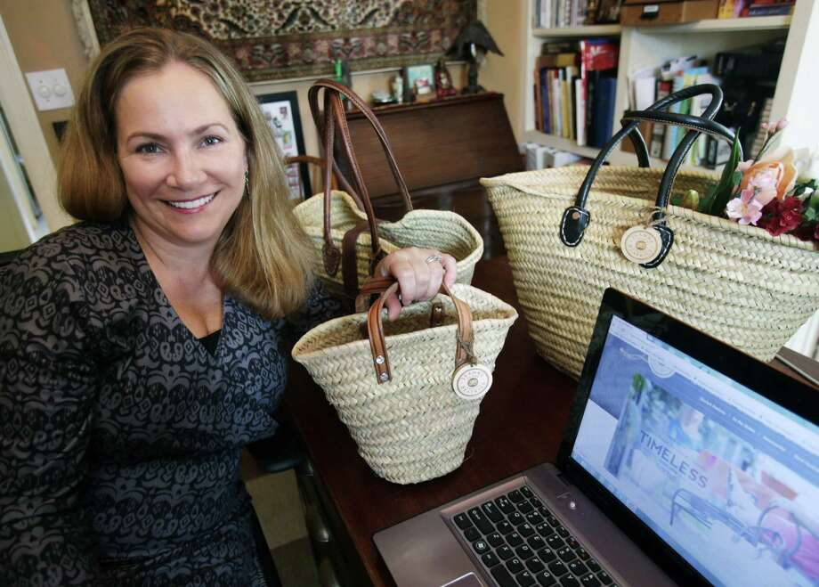 "FILE - In this Tuesday, March 4, 2014 photo, Laura Benson, who owns Jeanne Beatrice, a company that sells handmade baskets, poses with some of her basket creations in her home-based business in Edina, Minn. Benson was happy when her bank gave her an increase in her small business credit line. ""They just gave me the $7,000 without my asking,"" she said, with the increase coming a year after she got the $25,000 credit line for her business. (AP Photo/Jim Mone) ORG XMIT: MP101 Photo: Jim Mone / AP"