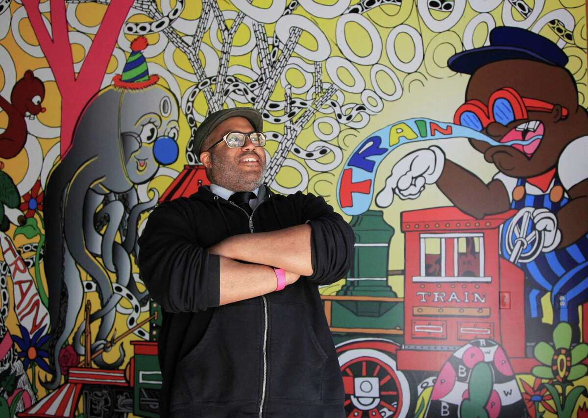 """Artist Trenton Doyle Hancock stands near his superhero alter-ego Torpedo Boy, one of dozens of fun characters he's drawn into """"Destination Mound Town,"""" a new mural installation for the Hermann Park train tunnel."""