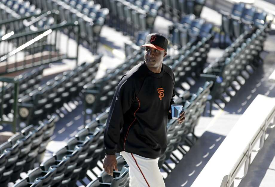 San Francisco Giants manager Bruce Bochy, left, listens as former player Barry Bonds arrives for a news conference before a spring training baseball game in Scottsdale, Ariz., Monday, March 10, 2014. Photo: Chris Carlson, Associated Press