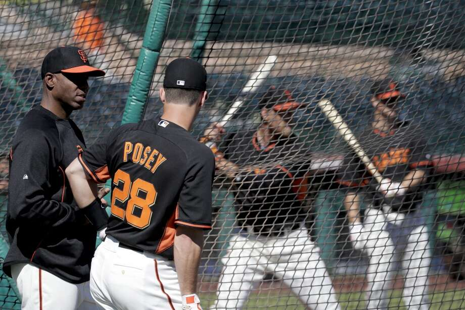 San Francisco Giants former player Barry Bonds, left, chats with catcher Buster Posey during batting practice before a spring training baseball game between the Giants and the Chicago Cubs in Scottsdale, Ariz., Monday, March 10, 2014. Photo: Chris Carlson, Associated Press