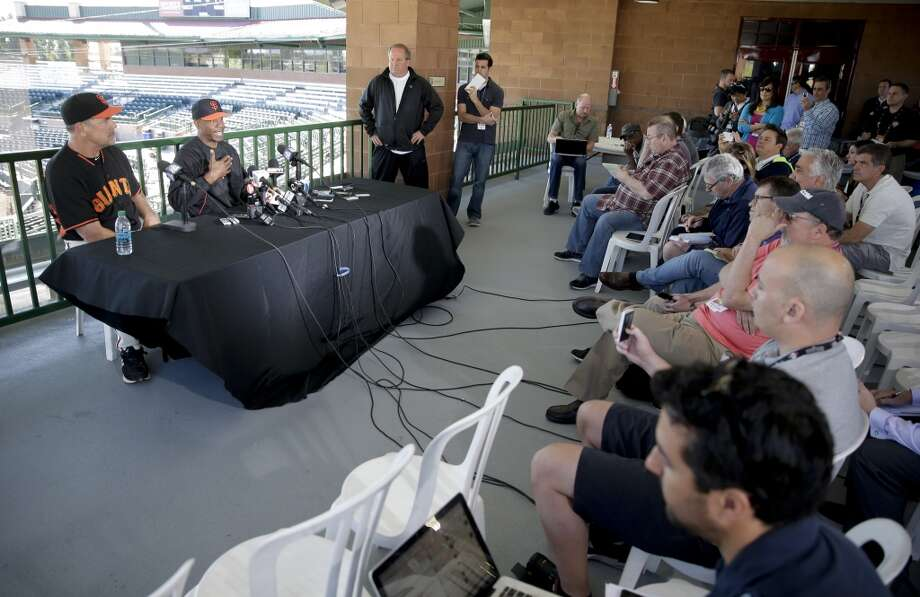 San Francisco Giants manager Bruce Bochy, left, listens as former player Barry Bonds speaks during a news conference before a spring training baseball game in Scottsdale, Ariz., Monday, March 10, 2014. Bonds starts a seven day coaching stint today. Photo: Chris Carlson, Associated Press