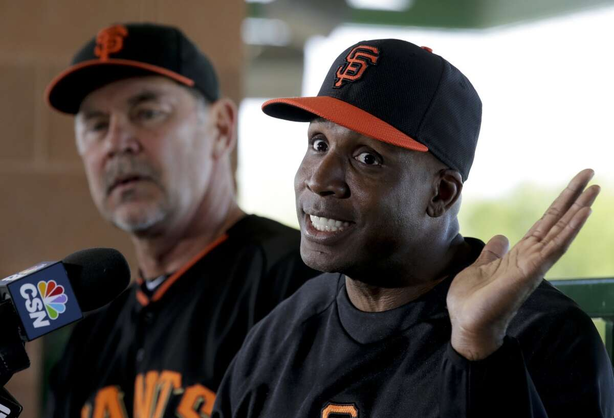 San Francisco Giants manager Bruce Bochy, left, listens as former player Barry Bonds speaks at a news conference before a spring training baseball game in Scottsdale, Ariz., Monday, March 10, 2014. Bonds starts a seven day coaching stint today.