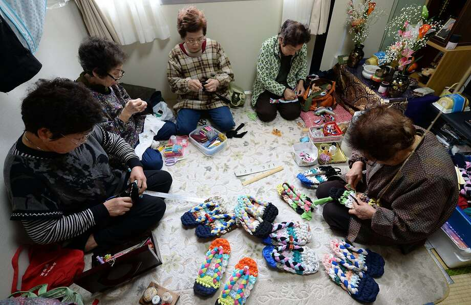 This picture taken on March 3, 2014 shows elderly women making sandals from used T-shirts in a small room of a temporary housing complex in Ishinomaki, Miyagi Prefecture. Since Japan's quake-tsunami disaster tens of thousands of refugees are still struggling to cope as the country gets set to mark the third anniversary of the disaster on March 11. The government has pledged billions of dollars in reconstruction funds but people are still struggling to make do in cramped temporary housing. Photo: Toru Yamanaka, AFP/Getty Images