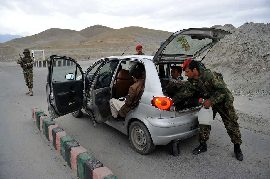 Afghan security personnel search a car at a checkpoint on the outskirts of Jalalabad in Nangarhar province on March 10, 2014. Afghanistan is due to hold presidential and provincial council elections in April this year. AFP PHOTO/ Noorullah ShirzadaNoorullah Shirzada/AFP/Getty Images Photo: Noorullah Shirzada, AFP/Getty Images