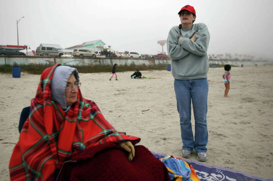 Earline Ischy, 80, stays warm while daughter Sarah Satterlee tries to warm up on a chilly afternoon on the beach during their spring break vacation on March 10, 2014, in Galveston. According to the National Weather Service, it's 52 degree at Galveston Island which is 10 degrees cooler then it was last year. Photo: Mayra Beltran, Houston Chronicle / © 2014 Houston Chronicle