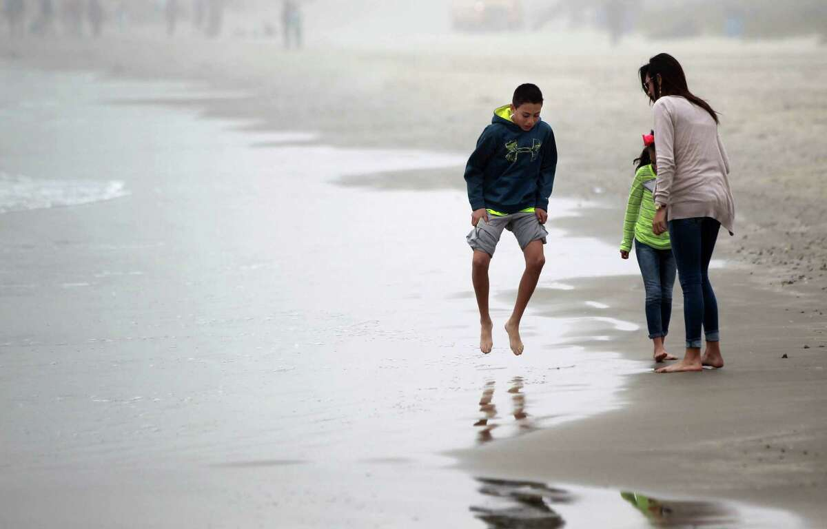 Sebastian Murguia, 12, jumps as his toes touch the cold water while vacationing on spring break with family sisters Nayeli Murguia, 8, and Emily Murguia, 17, on March 10, 2014, in Galveston.