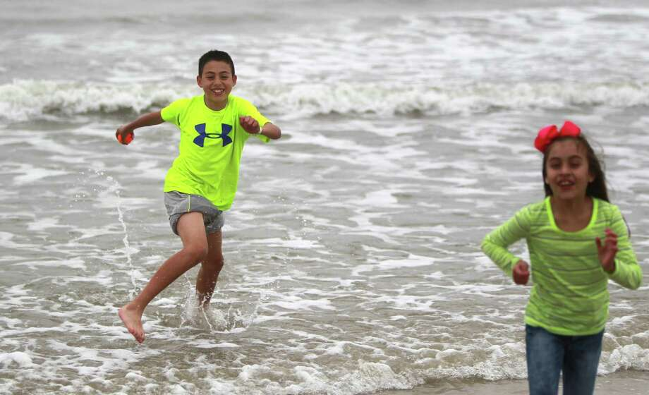 "Sebastian Murguia, 12, runs back to shore after collecting a loose ball in the cold water while playing with sister Nayeli Murguia, 8, on March 10, 2014, in Galveston. ""It's not your average spring break with swimsuits. It's pretty cold"", says Emily Murguia. According to the National Weather Service, it's 52 degree at Galveston Island which is 10 degrees cooler then it was last year. Photo: Mayra Beltran, Houston Chronicle / © 2014 Houston Chronicle"