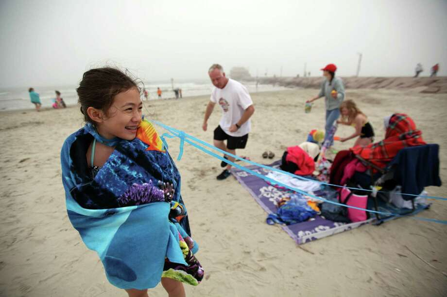 Jennifer Gantz, 12, tries to warm-up with her towel while flying kites during their spring break vacation on March 10, 2014, in Galveston. According to the National Weather Service, it's 52 degree at Galveston Island which is 10 degrees cooler then it was last year. Photo: Mayra Beltran, Houston Chronicle / © 2014 Houston Chronicle