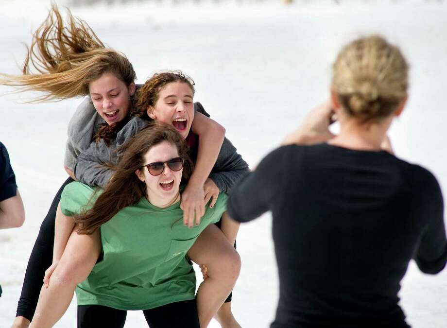 Destin, Florida doesn't look much warmer than Galveston. Sisters Zoe Bart, top, and Manon Bart, center, climb on the back of their friend, Alayna Flynn, for a photo by their mother, Sophie Bart, as they enjoy a visit to the beach Wednesday, March 5, 2014, at Pompano Joe's in Destin, Fla. The Florida panhandle community of Destin is a popular spring break destination for both families and college students.  (AP Photo/Northwest Florida Daily News, Devon Ravine) Photo: Devon Ravine, Associated Press / NORTHWEST FLORIDA DAILY NEWS