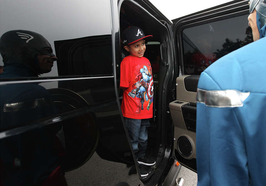 Andy Pardo, 6, smiles as looks out of a limousine to Michael Hill dressed as superhero Captain America at Mays Family YMCA on Friday, Mar. 7, 2014. Pardo was diagnosed with osteosarcoma - a cancer that has affected his left leg and has spread to his lungs. The cancer has become terminal for Pardo. In light of his terminal illness, the YMCA, the YMCA Texans youth football team and others have decided to help Pardo fulfill an early birthday wish: to be famous. That wish came together and was celebrated with superheroes, games, music and a ride in a limousine.