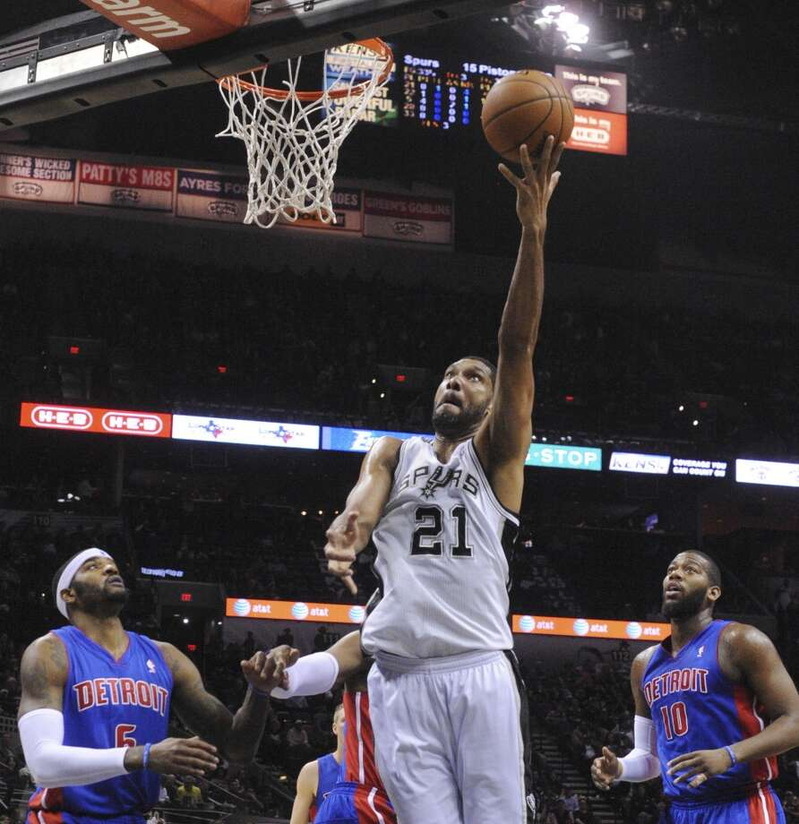 Tim Duncan of the San Antonio Spurs lays up the ball against the Detroit Pistons during NBA action in the AT&T Center on Wednesday, Feb. 26, 2014. Kentavious Caldwell-Pope, left, and Greg Monroe of the Pistons watch. Photo: Billy Calzada, San Antonio Express-News