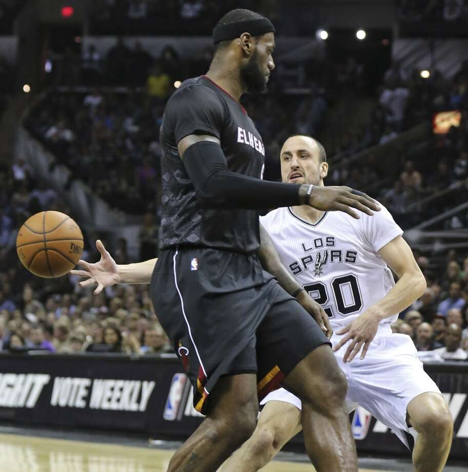 San Antonio Spurs' Manu Ginobili pass around Miami Heat's LeBron James during second half action Thursday March 6, 2014 at the AT&T Center. The Spurs won 111-87. Photo: Edward A. Ornelas, San Antonio Express-News