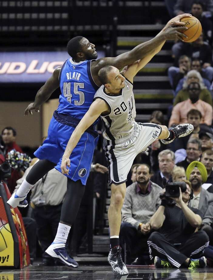 Dallas Mavericks' DeJuan Blair and San Antonio Spurs' Manu Ginobili grab for a rebound during first half action Sunday March 2, 2014 at the AT&T Center. Photo: Edward A. Ornelas, San Antonio Express-News