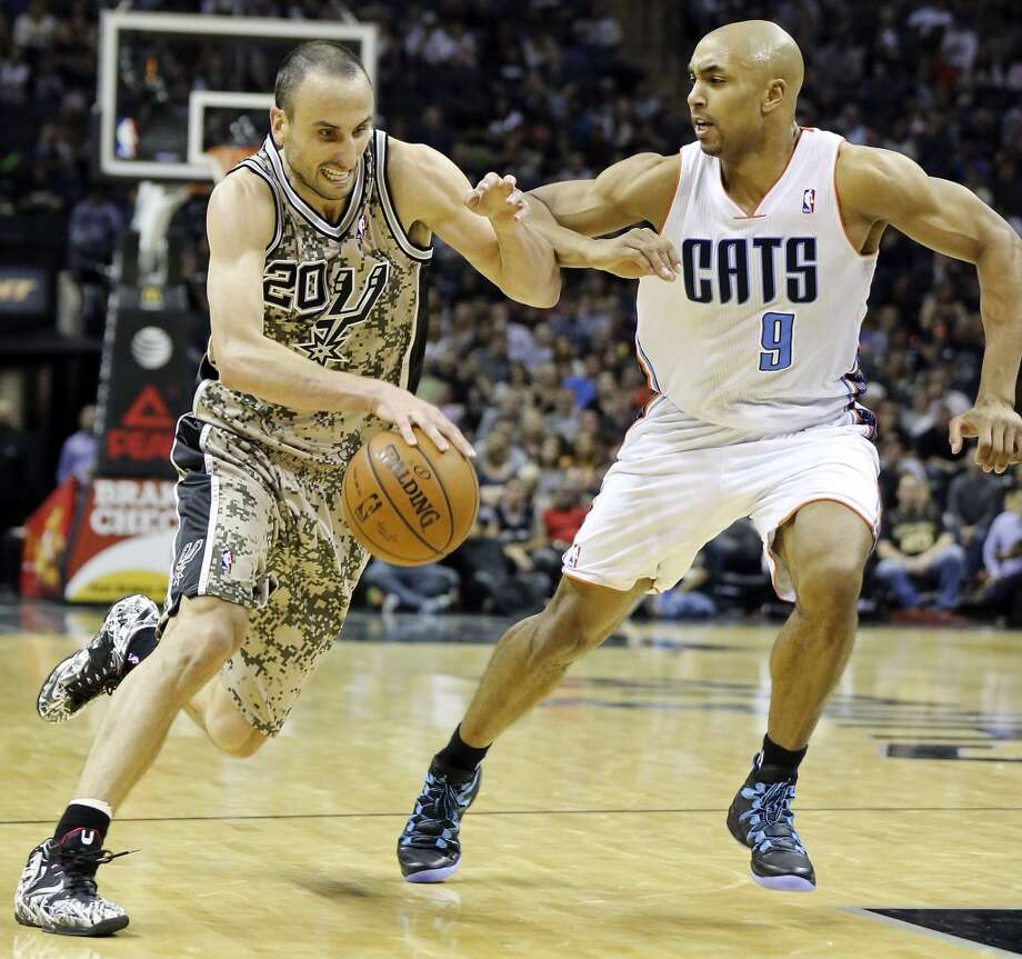 San Antonio Spurs' Manu Ginobili looks for room around Charlotte Bobcats' Gerald Henderson during second half action Friday Feb. 28, 2014 at the AT&T Center. The Spurs won 92-82. Photo: Edward A. Ornelas, San Antonio Express-News