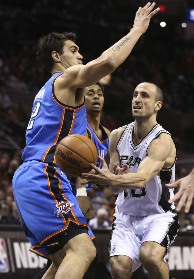 San Antonio Spurs' Manu Ginobili passes the ball around Oklahoma City Thunder's Steven Adams during the first half at the AT&T Center, Wednesday, Jan. 22, 2014. Photo: Jerry Lara, San Antonio Express-News