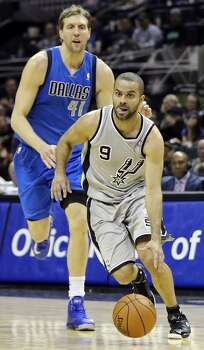 San Antonio Spurs' Tony Parker drives to the basket around Dallas Mavericks' Dirk Nowitzki during second half action Sunday March 2, 2014 at the AT&T Center. The Spurs won 112-106. Photo: Edward A. Ornelas, San Antonio Express-News