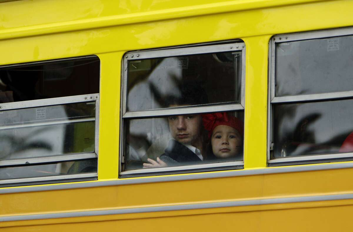 Two children ride a Muni F Line streetcar as it turns onto Market Street in San Francisco, Calif., on Wednesday, March 5, 2014. Muni F Line of historic streetcars is popular with both tourists who tour the city and locals who use them for commute. But there is a suggestion that fares might go up to a premium rate of $6 like the Cable Cars, instead of the standard Muni $2 fare that is paid today.