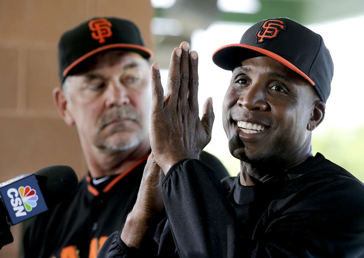 San Francisco Giants manager Bruce Bochy, left, listens as former player Barry Bonds speaks during a news conference before a spring training baseball game in Scottsdale, Ariz., Monday, March 10, 2014. Bonds starts a seven day coaching stint today. (AP Photo/Chris Carlson)