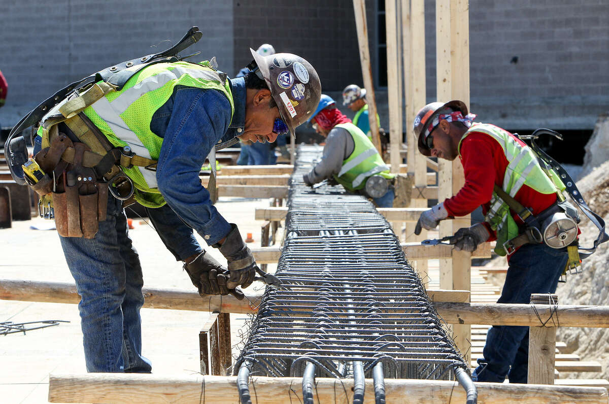 Construction workers tie rebar for a beam in the new cafeteria at Highlands High School in late February.