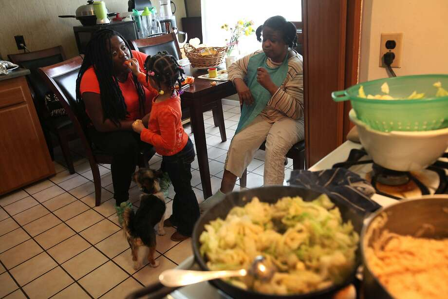 Ariyahn Hills feeds her aunt Rheema Calloway an orange slice, top, as the two and Calloway's aunt Kamala Lucas wait for dinner to be served. Photo: Leah Millis, The Chronicle