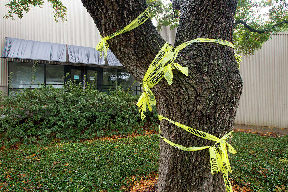 A tree wrapped in caution tape is seen in front of the Martel Center,