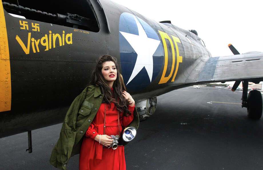 "Jolene Salinas has her picture made Monday March 10, 2014 next to the ""Memphis Belle"" World War II era B-17G bomber. The plane is run by the Liberty Foundation in Oklahoma and was featured in the movie ""Memphis Belle."" The plane will be at Stinson Field until next Sunday. Photo: JOHN DAVENPORT, SAN ANTONIO EXPRESS-NEWS / ©San Antonio Express-News/Photo may be sold to the public"