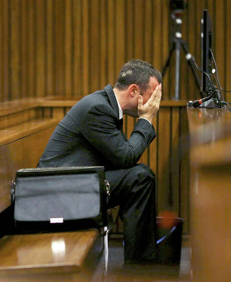 Oscar Pistorius covers his face as he listens to cross-examination in court about the events surrounding the death of his girlfriend Reeva Steenkamp. Photo: Siphiwe Sibeki, POOL / POOL reuters
